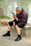 Pengzhou, China: Elderly Man Reading Newspaper Royalty Free Stock Images