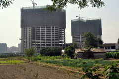 Pengzhou, China: Farm & New Apartment Bldgs. A farmer's field and house are dwarfed by the ever-encroaching spread of building as luxury high-rise apartment Stock Photos