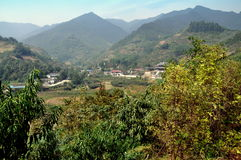 Pengzhou, China: Farmlands, Village and Temple. View to a lush farmlands valley with a small Taoist temple and nearby village with distant Sichuan province Royalty Free Stock Images