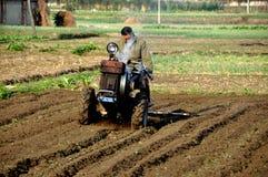 Pengzhou, China: Fazendeiro que ara o campo Imagens de Stock