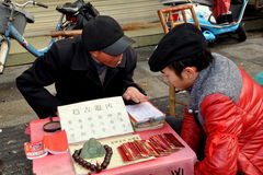 Pengzhou, China: Fortune Teller in Long Xing Square. Man in a red jacket listens as a fortune teller in Long Xing Square predicts his future for the Year of the Royalty Free Stock Photography