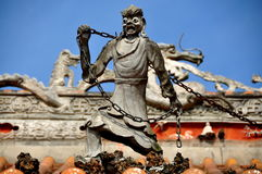 Pengzhou, China: Ghost Figure on Shi Fo Temple. A sculpted ghost statue bearing an iron chain stands atop the roof of the great hall at the Shi Fo Buddhist Royalty Free Stock Images