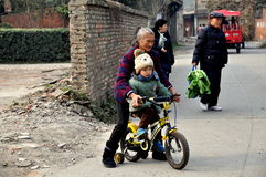 Pengzhou, China: Grandmother Teaching Child to Ride Bike Stock Photography