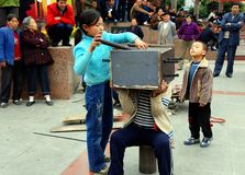 Pengzhou, China: Kids Performing Magic Tricks. A little girl working with her younger brother inserts knives into a wooden box placed over his head as they royalty free stock photo