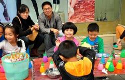 Pengzhou, China: Kinder, die Figürchen malen lizenzfreies stockbild