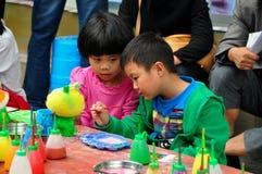 Pengzhou, China: Kinder, die Figürchen malen lizenzfreies stockfoto