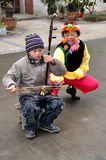 Pengzhou, China: Little Boy Playing Erhu. A little boy playing the Erhu musical instrument while a woman in traditional Yi People clothing holds a microphone to stock images