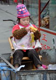 Pengzhou, China: Little Girl and Barbie Doll. A little Chinese girl sitting in the back of a bicycle cart plays with her plastic Barbie doll in Pengzhou, China royalty free stock photos