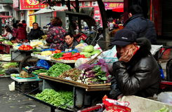 Pengzhou, China: Long Xing Market Farmers. Farmers display their farm-fresh produce from small bicycle carts as they wait for customers at the Long Xing Royalty Free Stock Images