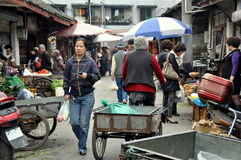 Pengzhou, China: Long Xing Marketplace. Farmers offer their various food products and vegetables in a narrow, bustling lane at the Long Xing outdoor marketplace Royalty Free Stock Photography