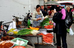 Pengzhou, China: Long Xing Marketplace. Woman chatting on her cellphone stops to check a dazzling array of colourful, farm-fresh produce at the busy outdoor Long Stock Photography