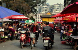 Pengzhou, China: Long Xing Outdoor Market. The bustling outdoor Long Xing marketplace lined with umbrellas shading farmers selling farm fresh produce in Pengzhou Stock Photos