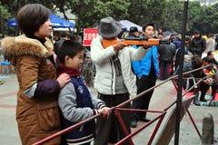 Pengzhou, China: Man with Gun at Game Booth Stock Image