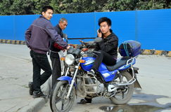Pengzhou, China: Man on Motorcycle with Cellphone Stock Images