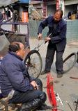 Pengzhou, China: Man Repairing Pedicab Tire Royalty Free Stock Photo