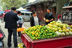 Pengzhou, China: Man Selling Citrus Fruits. Man selling pomelos and oranges from the back of his pickup truck at the Tian Fu outdoor marketplace in Pengzhou Stock Photos