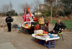 Pengzhou, China: Man Selling Fireworks and Sundries. Man sitting by the edge of a small lane selling sundries along with incense sticks and Chinese New Year Stock Photography