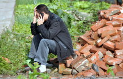 Pengzhou, China: Man Using Cellphone. Man sitting on a pile of bricks looks distraught while talking on his cellphone alongside a country road near Pengzhou Royalty Free Stock Images