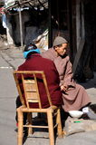 Pengzhou, China: Monk & Woman Sitting in Front of Home Royalty Free Stock Photo