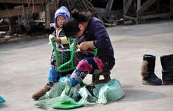 Pengzhou, China: Mother Repairing Chair Royalty Free Stock Images