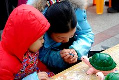 Pengzhou, China: Mother & Son Painting Turtle Royalty Free Stock Photography