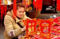 Pengzhou, China: Mujer con las decoraciones chinas del Año Nuevo Imagen de archivo