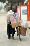 Pengzhou, China: Old Man Walking his Bicycle. An old man walking his bicycle laden with boxes and bags of food along a small country road near Pengzhou, China Royalty Free Stock Photos