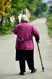 Pengzhou, China: Old Woman Walking on Road Royalty Free Stock Photo
