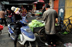 Pengzhou, China: People at Long Xing Outdoor Marketplace. Woman on her motorcycle stops to buy cabbage from a vendor at the Long Xing outdoor marketplace in Stock Photo