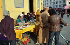 Pengzhou, China: People in Long Xing Square. Woman selling hand-made jewelry, necklaces, and religious objects in front of the Long Xing Temple entrance pavilion Royalty Free Stock Image