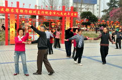 Pengzhou, China: Seniors Dancing in Park. Seniors dancing together in the open plaza of Pengzhou Park filled with red lanterns and signs in honour of Chinese New Royalty Free Stock Images