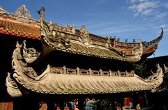 Pengzhou, China: Shi Fo Buddhist Temple. Decorative flying eave roofs on both an incense burner and great hall at the Shi Fo Buddhist countryside temple in Stock Photo
