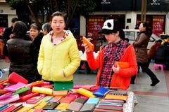 Pengzhou, China: Teenaged Girls Shopping. Two teenaged girls shopping for bargain-priced wallets sold by a street vendor in Pengzhou, China's New Square Stock Photo