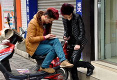 Pengzhou, China: Teens Checking Their Cellphones. PENGZHOU, CHINA:  Two Chinese teenagers with trendy clothes and hairstyles checking their cellphones in front Royalty Free Stock Photo