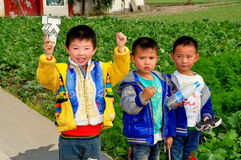 Pengzhou, China: Three Little Boys on Farm. Three little Chinese boys holding toys and a water bottle on a Sichuan province farm in Pengzhou, China stock image