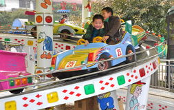 Pengzhou, China: Two Kids at Amusement Park. Two little boys having fun riding in a motorised car at an amusement park ride in Pengzhou Park in Pengzhou, China Royalty Free Stock Image