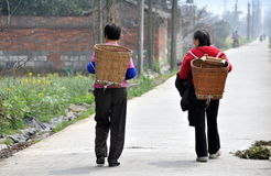 Pengzhou, China: Two Women on Country Road. Two women walking along a country road outside the city of Pengzhou, China carrying wicker harvesting baskets on stock photography