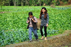 Pengzhou, China: Two Women on a Farm. Two women, one carrying a straw basket and the other barefoot, walking along an earthen berm separating fields of crops on Stock Photo