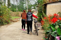 Pengzhou, China: Two Women Walking Bikes on Country Road Royalty Free Stock Images