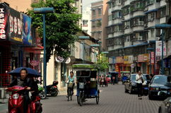 Pengzhou, China: View of Shang Sheng Street. View along Shang Sheng Street lined with typical Chinese stores, parked cars, motorcycles, apartment buildings, and Stock Photography