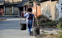 Pengzhou, China: Woman Carrying Water Buckets Stock Images
