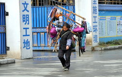 Pengzhou, China: Woman Selling Sundries. A woman carrying her portable store with all manner of notions and sundries hung from bamboo poles walks along a city Stock Image