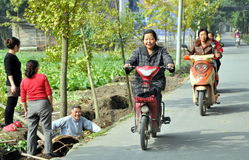 Pengzhou, China: Women on Mopeds Stock Photo