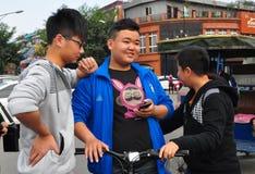 Pengzhou, Chine : Ados avec le téléphone portable Images stock