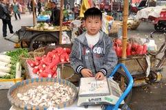 Pengzhou, Chine : Jeune garçon vendant des champignons de couche image libre de droits