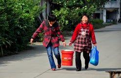Pengzhou, Chiny: Dwa kobiety Niesie wiadro Fotografia Royalty Free