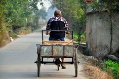 Pengzhou, Chiny: Rolnik Peddles jego Rowerową furę wzdłuż wiejskiej drogi Obraz Royalty Free