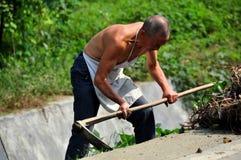 Pengzhou, Cina: Agricoltore con la zappa del lavoro Fotografie Stock Libere da Diritti