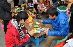 Pengzhou, Cina: Bambini che verniciano il drago dell'intonaco Immagine Stock