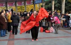 Pengzhou, Cina: Canto della donna con le sete rosse Fotografia Stock